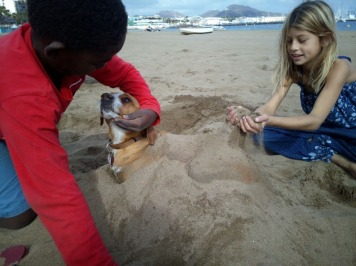 Kids playing with dog at the beach